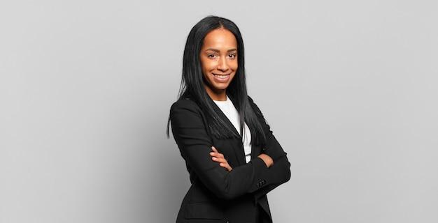 Mulher jovem sorrindo para a câmera com os braços cruzados e uma expressão feliz, confiante e satisfeita, vista lateral