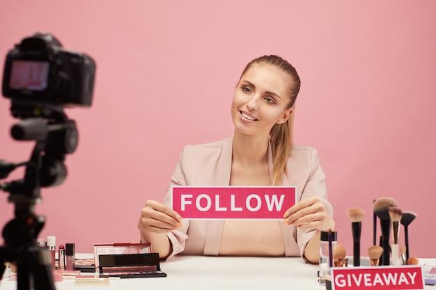 Mulher jovem sorrindo para a câmera e diz aos seguidores para seguirem seu blog de beleza