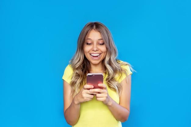 Mulher jovem sorrindo segurando um telefone celular, olhando para a tela isolada em um fundo de cor azul