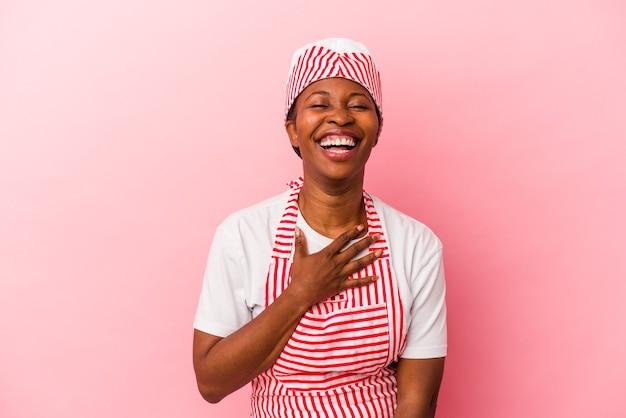Mulher jovem sorveteira afro-americana isolada em fundo rosa ri alto, mantendo a mão no peito.
