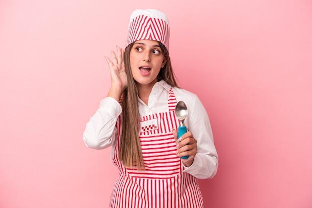 Mulher jovem sorveteira segurando colher isolada no fundo rosa, tentando ouvir uma fofoca.