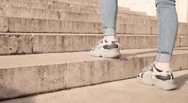 Mulher jovem subindo as escadas na cidade.