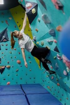 Mulher jovem subindo na parede de treino no ginásio