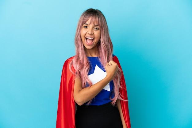 Mulher jovem super-heroína com cabelo rosa isolado em um fundo azul comemorando uma vitória