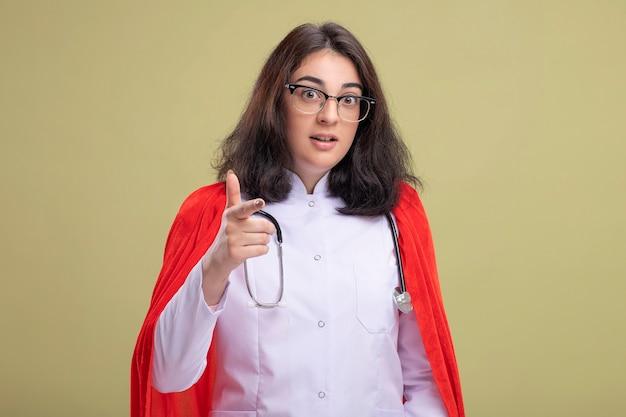 Mulher jovem super-heroína impressionada com uma capa vermelha, vestindo uniforme de médico e estetoscópio com óculos, olhando e apontando para a frente, isolada na parede verde oliva com espaço de cópia