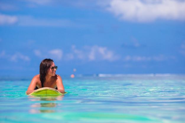 Mulher jovem surfista surfando durante férias na praia
