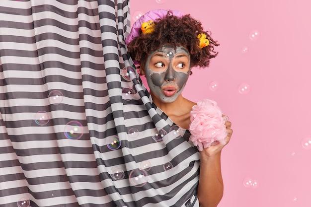 Mulher jovem surpresa com cabelo encaracolado aplica máscara de argila de beleza no rosto parece de lado segura a esponja de banho gosta de tomar banho em poses de ducha se esconde atrás de uma cortina de bolhas de sabão ao redor