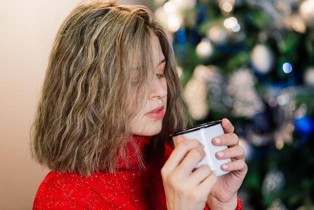 Mulher jovem surpresa emocional feliz por uma árvore de natal na aconchegante sala de estar, o conceito de felicidade