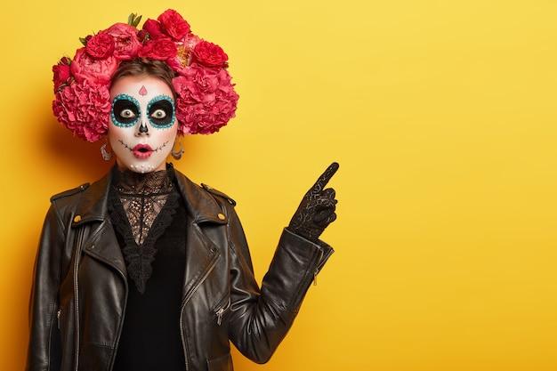 Mulher jovem surpresa tem imagem de fantasma assustador, rosto de caveira de argila, maquiagem profissional usa guirlanda vermelha feita de flores cheirosas apontando com expressão de medo