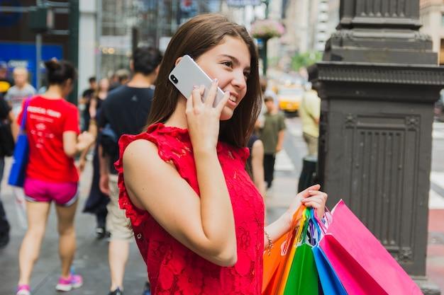 Mulher jovem, telefonando, com, bolsas para compras