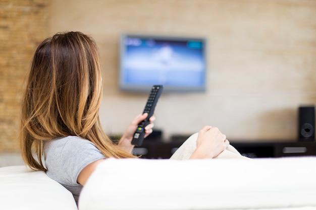 Mulher jovem, televisão assistindo