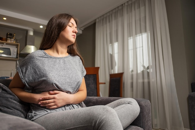 Mulher jovem tem dor no hipocôndrio direito, mulher jovem tem dor de estômago, doença da vesícula biliar
