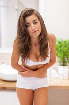Mulher jovem tem problemas com dor de estômago