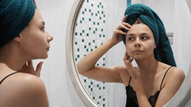 Mulher jovem tem problemas de pele no rosto - ela se olha no espelho no banheiro