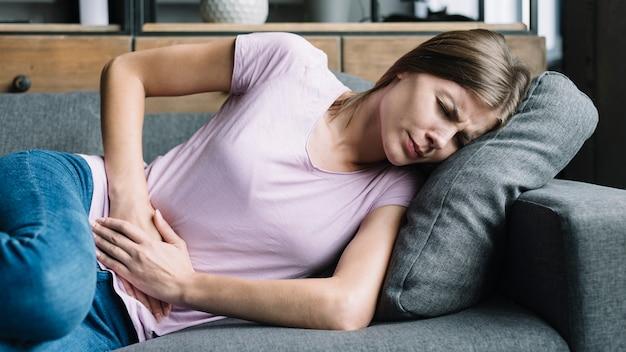 Mulher jovem, tendo, dor estômago, mentindo, ligado, sofá