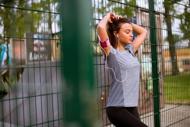 Mulher jovem, tendo, exercício, ao ar livre