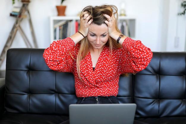 Mulher jovem, tendo, problemas, com, laptop, enquanto, sentando, ligado, um, couro, sofá
