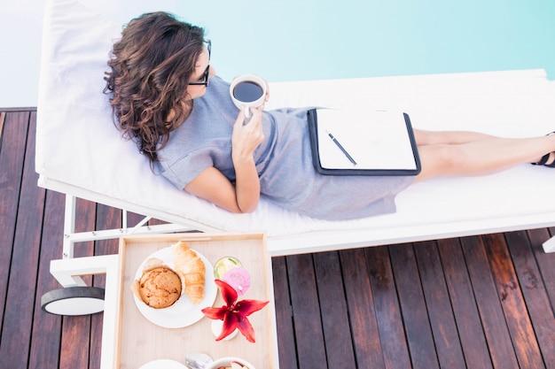 Mulher jovem, tendo, xícara chá, e, relaxante, ligado, um, lounger sol, perto, poolside