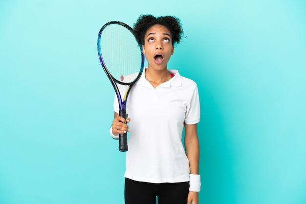 Mulher jovem tenista isolada em um fundo azul, olhando para cima e com expressão de surpresa