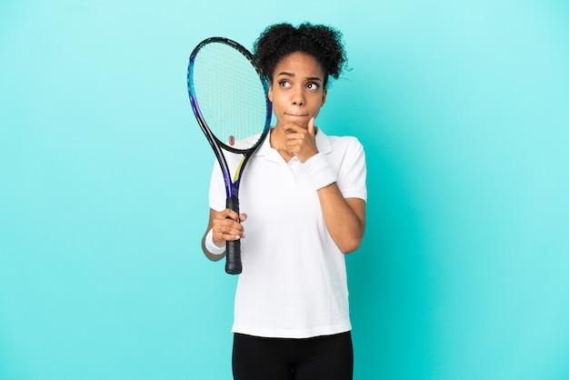 Mulher jovem tenista isolada em um fundo azul, tendo dúvidas e pensando