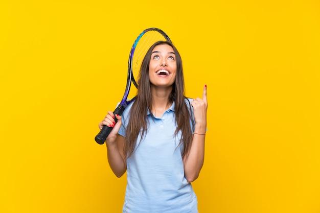 Mulher jovem tenista isolado parede amarela apontando uma ótima idéia