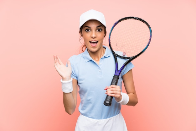 Mulher jovem tenista isolado parede rosa com expressão facial chocado