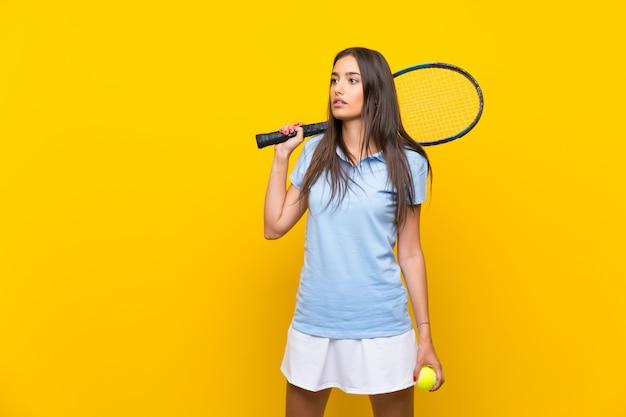 Mulher jovem tenista sobre parede amarela isolada