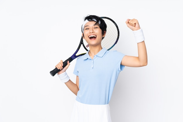 Mulher jovem tenista vietnamita sobre parede branca isolada, jogando tênis e comemorando uma vitória