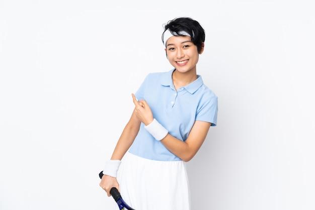 Mulher jovem tenista vietnamita sobre parede branca jogando tênis e apontando para a lateral
