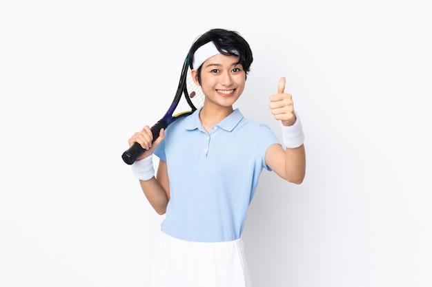 Mulher jovem tenista vietnamita sobre parede branca, jogando tênis e com o polegar para cima