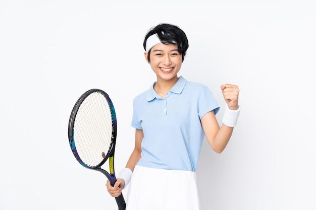 Mulher jovem tenista vietnamita sobre parede branca, jogando tênis e comemorando uma vitória