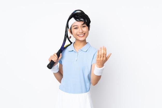 Mulher jovem tenista vietnamita sobre parede branca, jogando tênis e fazendo gesto próximo