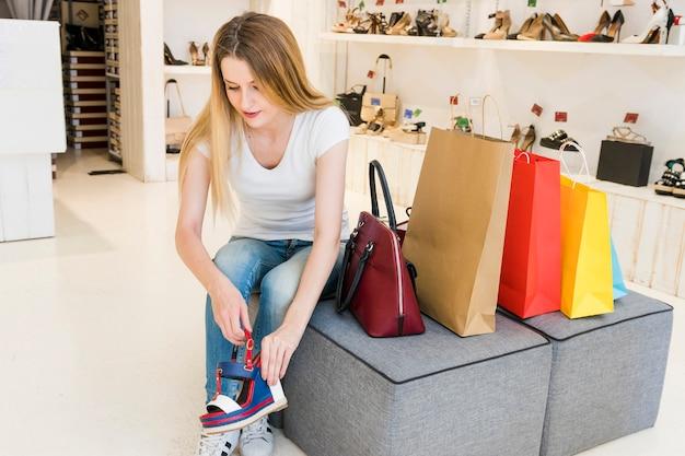 Mulher jovem, tentando, calçado, em, sapato, loja