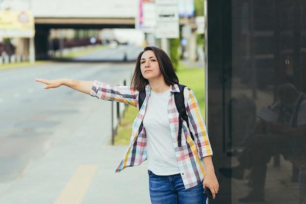 Mulher jovem tentando pegar um táxi em um ponto de ônibus usando um aplicativo de um telefone celular