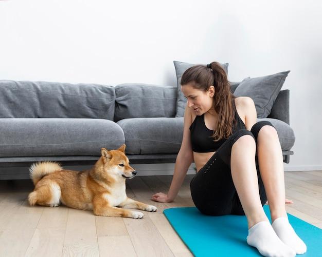 Mulher jovem tentando praticar esportes em casa com o cachorro