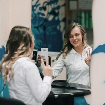 Mulher jovem tira uma selfie em um salão de beleza. o conceito de estilo de vida