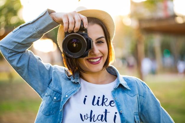 Mulher jovem tirando fotos com uma câmera profissional no parque verde de verão
