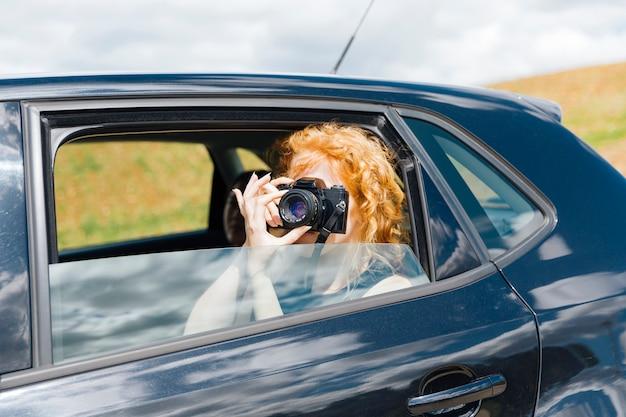 Mulher jovem, tirando, fotos, ligado, câmara