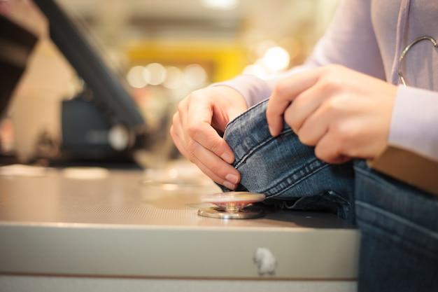 Mulher jovem tirando o pino magnético da calça jeans e se preparando para um cliente em um enorme shopping center