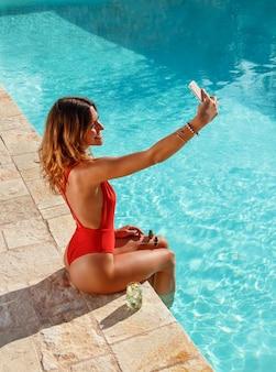 Mulher jovem tirando uma selfie na beira de uma piscina
