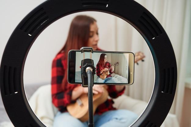 Mulher jovem toca discos de ukulele na câmera do telefone e o músico faz um concerto ao vivo em casa