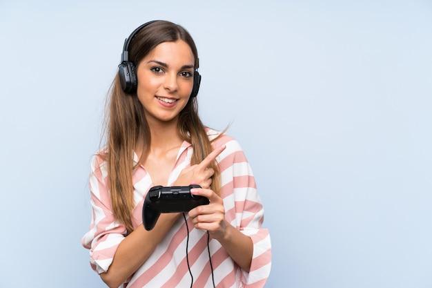 Mulher jovem, tocando, com, um, jogo video, controlador, isolado, parede azul, apontar ao lado, apresentar, um, produto