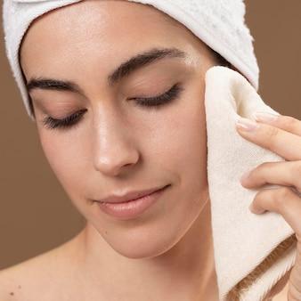 Mulher jovem tocando o rosto com uma toalha