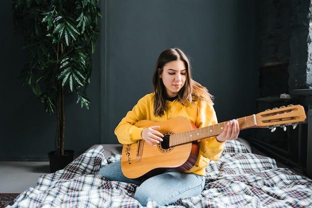 Mulher jovem tocando violão em casa, sentada na cama