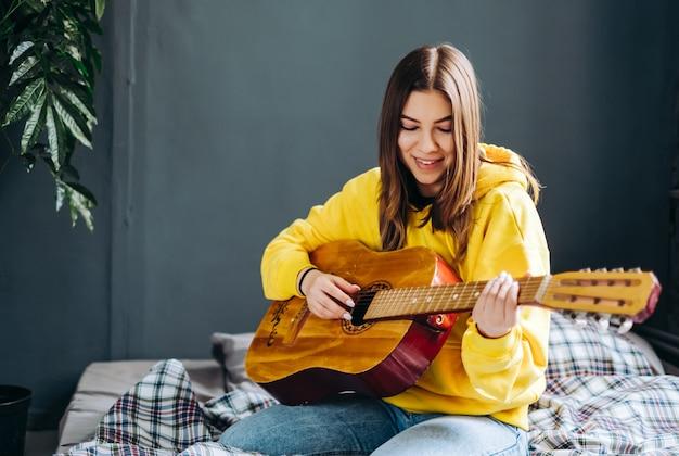 Mulher jovem tocando violão em casa
