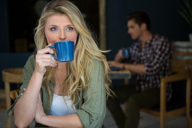 Mulher jovem tomando café com um homem sentado no fundo do refeitório