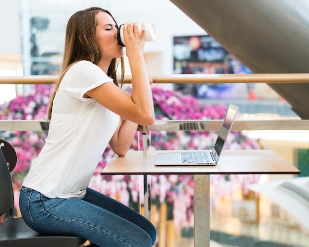 Mulher jovem tomando café com vista lateral