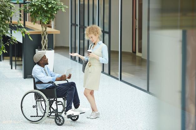Mulher jovem tomando café e conversando com um homem africano que, sentado em uma cadeira de rodas, está no shopping