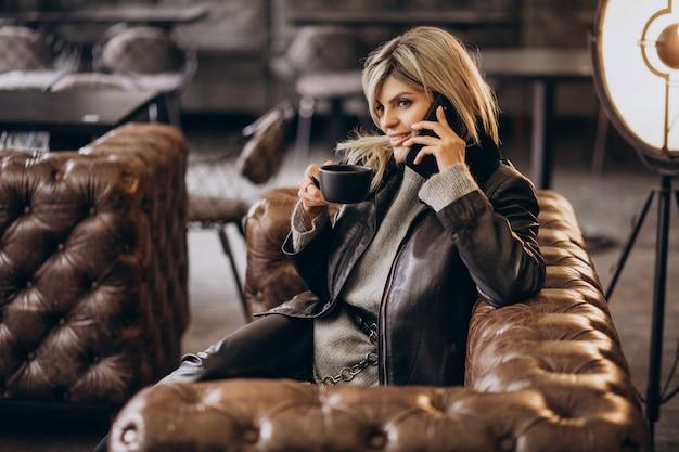 Mulher jovem tomando café e falando ao telefone em um café