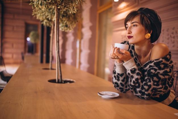 Mulher jovem tomando café em um café